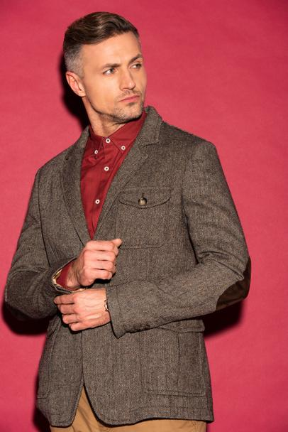 handsome man in formal wear looking away while adjusting jacket on red background - Photo, Image