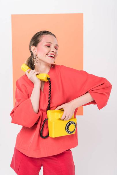 happy stylish girl holding retro telephone and posing with living coral on background - Photo, Image