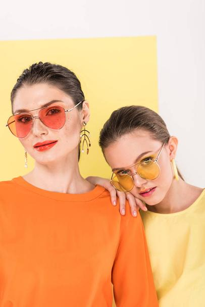 beautiful stylish girls in sunglasses looking at camera and posing with limelight on background - Photo, Image