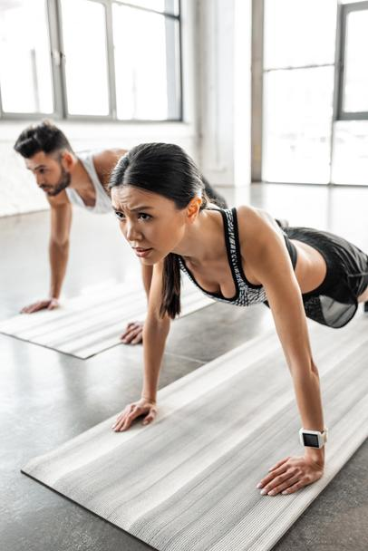 concentrated young woman and man doing push ups on yoga mats in gym  - Photo, Image