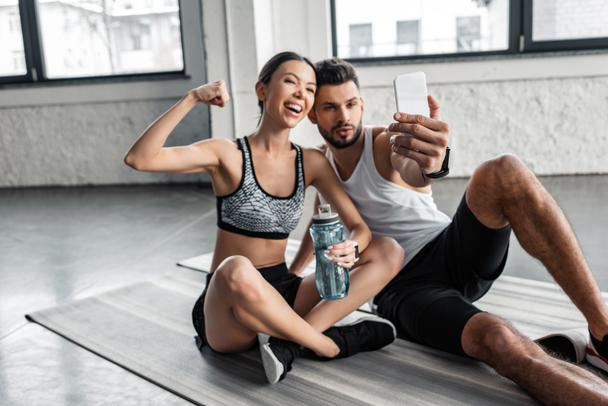 happy young couple in sportswear taking selfie with smartphone while resting on yoga mats after workout in gym   - Photo, Image