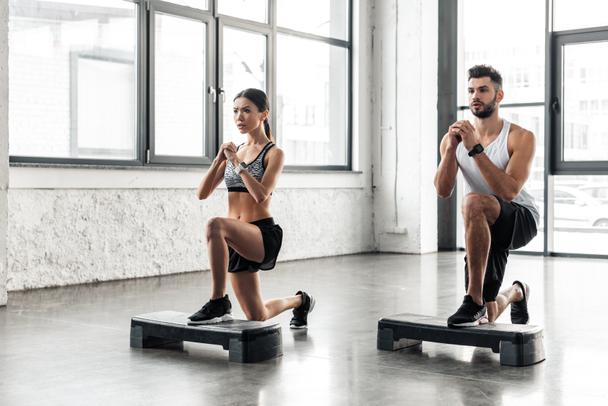 muscular young man and beautiful sporty girl training on step platforms in gym - Photo, Image