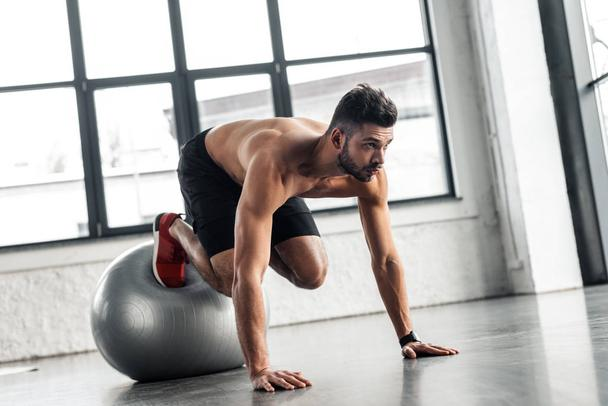 young bare-chested sportsman exercising on fitness ball in gym - Photo, Image