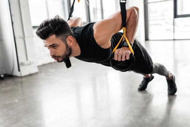 athletic handsome young sportsman exercising with resistance bands in gym - Photo, Image