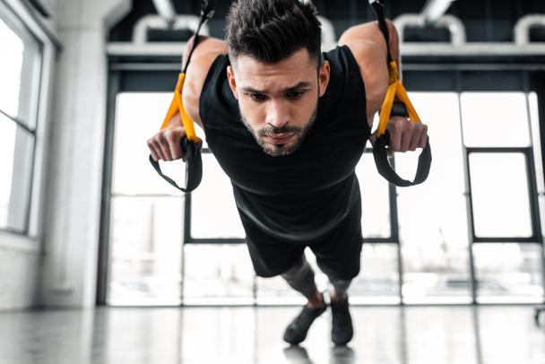 focused muscular young sportsman exercising with suspension straps in gym - Photo, Image