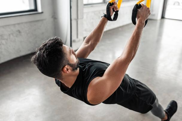muscular young man in sportswear training with suspension straps in gym  - Photo, Image