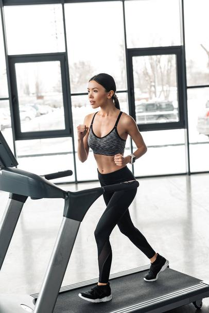 beautiful young sportswoman running on treadmill in gym  - Photo, Image
