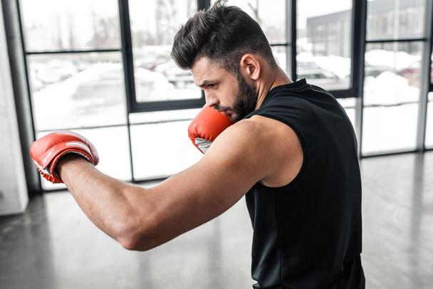 side view of handsome sporty young man in boxing gloves training in gym  - Photo, Image