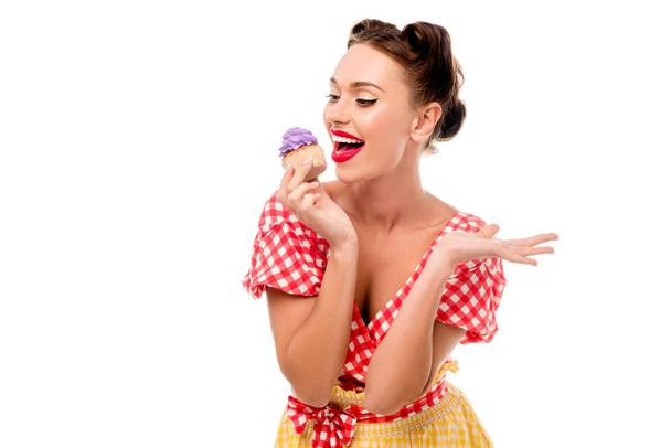 Pretty pin up girl tasting cupcake with purple cream isolated on white - Photo, Image