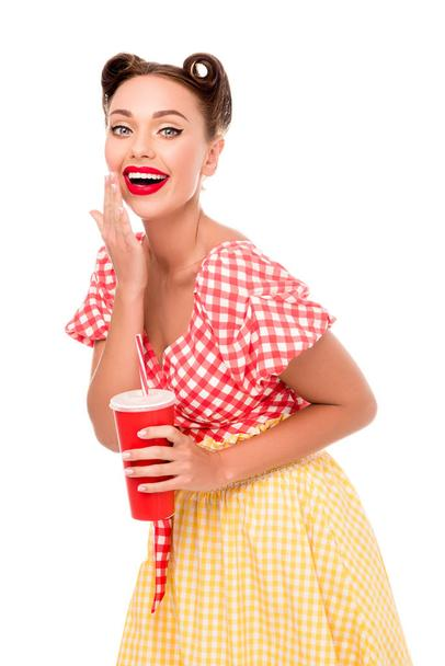 Smiling pretty pin up girl drinking from red paper cup with straw isolated on white - Photo, Image