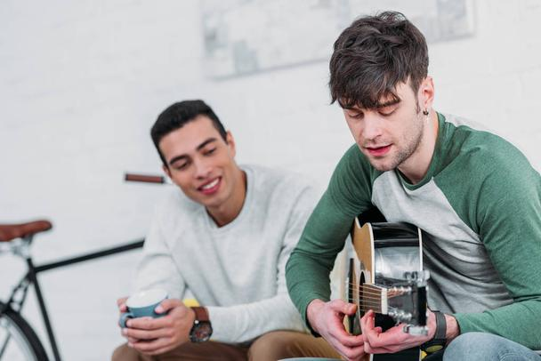 handsome young man playing guitar to mixed race friend  - Photo, Image