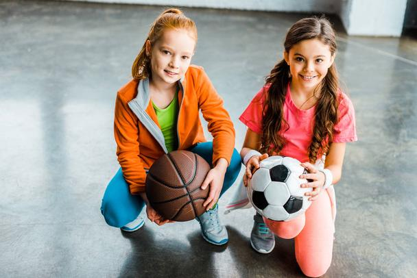 Cute kids holding soccer and basketball balls - Photo, Image