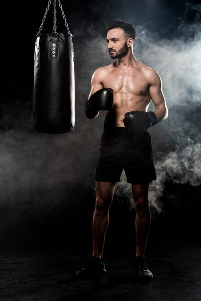 thoughtful sportsman in boxing gloves standing near punching bag on black with smoke - Photo, Image