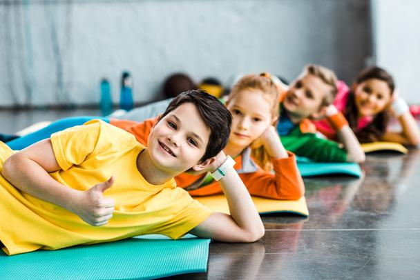 Cheerful kids lying on fitness mats in gym - Photo, Image
