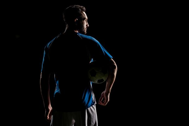 silhouette of muscular sportsman holding ball isolated on black - Photo, Image