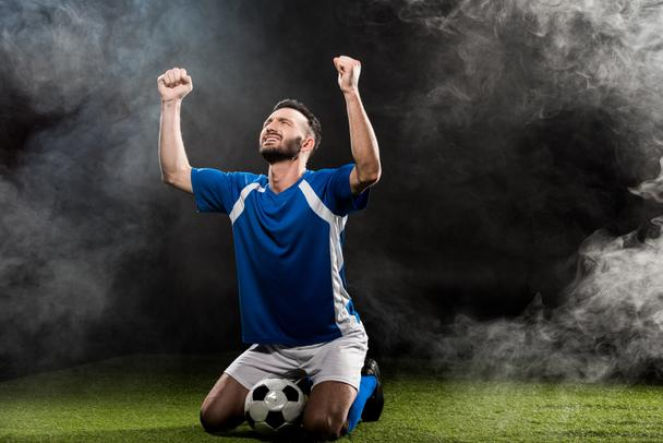 handsome football player celebrating victory while sitting on grass on black with smoke - Photo, Image