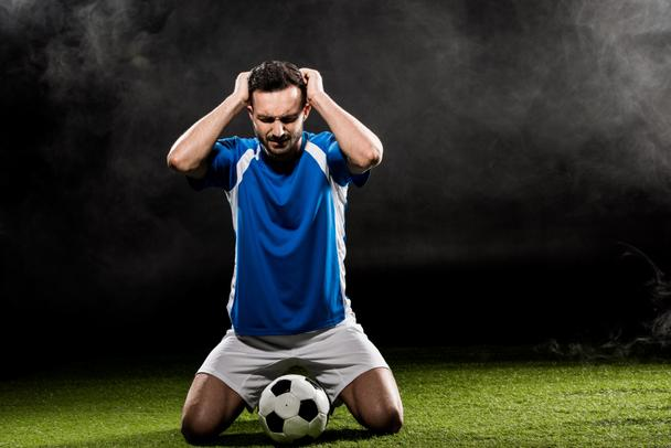 handsome football player holding head while sitting on grass on black with smoke - Photo, Image
