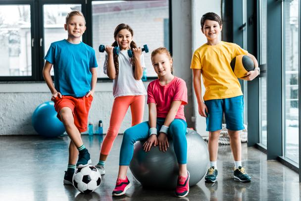 Laughing preteen kids posing with sport equipment - Photo, Image