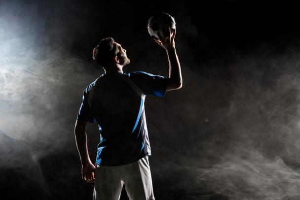 silhouette of player in uniform holding ball above head on black with smoke   - Photo, Image