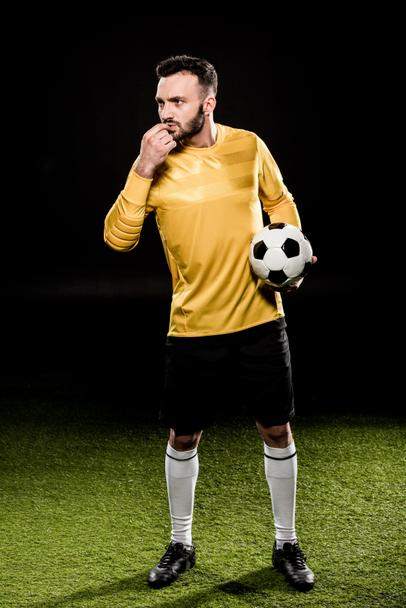 handsome bearded coach blowing whistle while holding ball isolated on black - Photo, Image