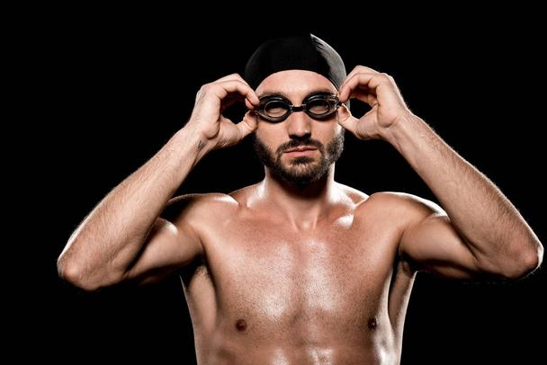 confident swimmer standing in swimming cap and touching goggles isolated on black  - Photo, Image