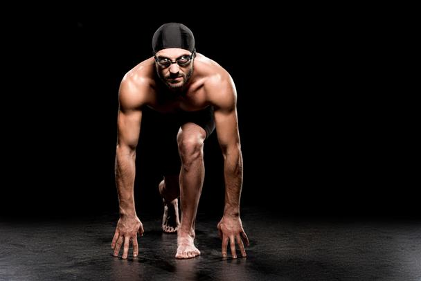 handsome swimmer standing in start position on black background  - Photo, Image
