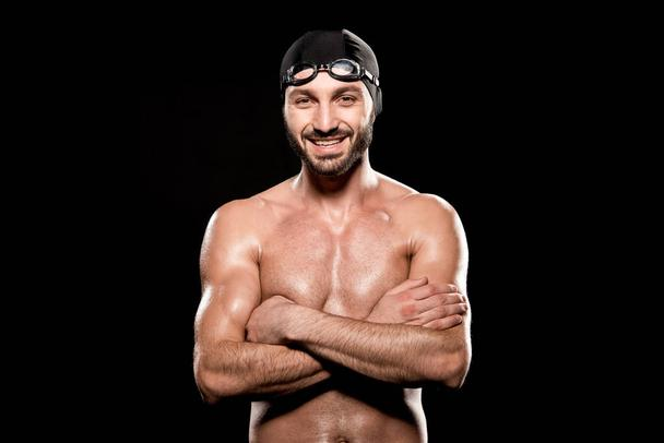happy swimmer standing with crossed arms isolated on black - Photo, Image