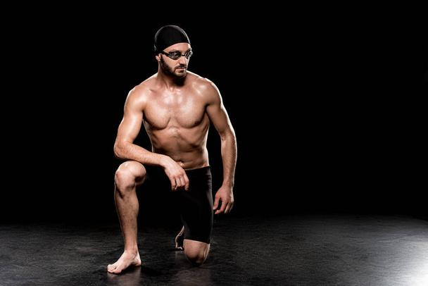 athletic sportsman sitting in swimming cap and goggles on black background - Photo, Image