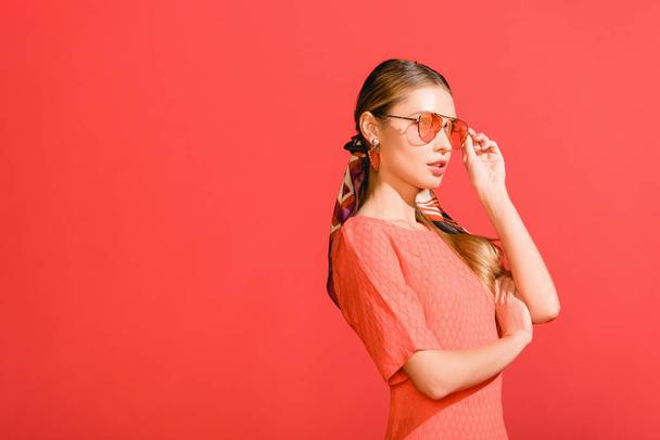 fashionable girl posing in living coral dress and sunglasses isolated on red background - Photo, Image