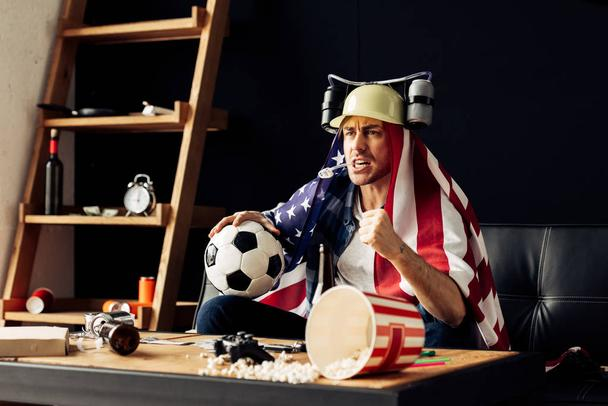 man wearing beer helmet drinking and holding ball while sitting with american flag on shoulders and watching game - Photo, Image