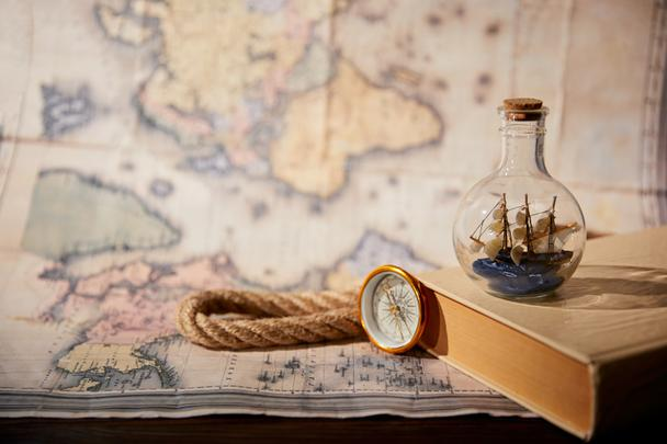 Selective focus of toy ship in glass bottle, book, map, compass and rope  - Photo, Image