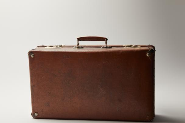 vintage leather brown suitcase on grey background  - Photo, Image