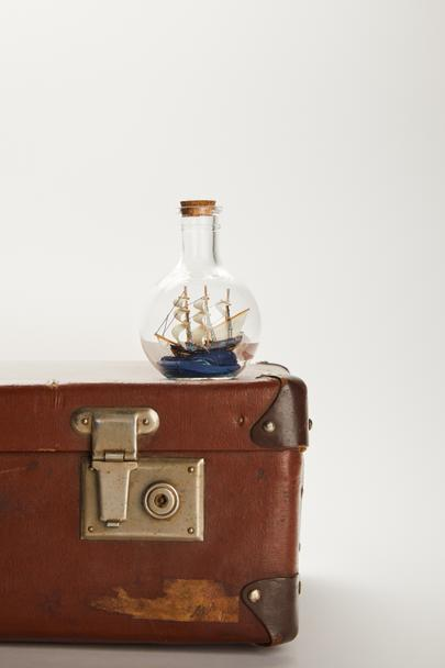 toy ship in glass bottle on brown suitcase with copy space  - Photo, Image