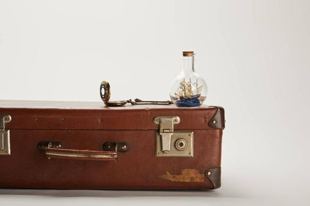 toy ship in glass bottle and compass on vintage brown suitcase with copy space  - Photo, Image