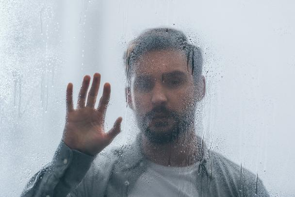 selective focus of raindrops on window with upset man on background - Photo, Image