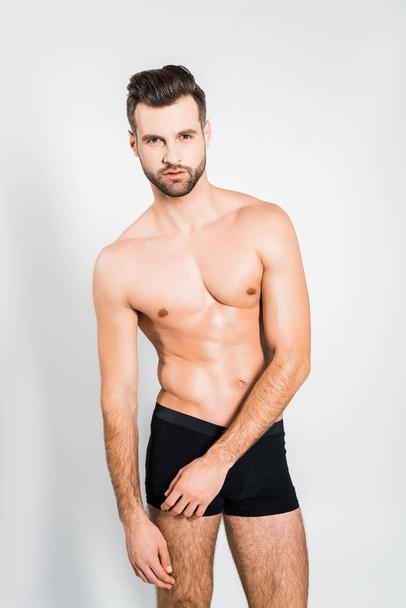 handsome man in black boxer shorts posing isolated on grey - Photo, Image