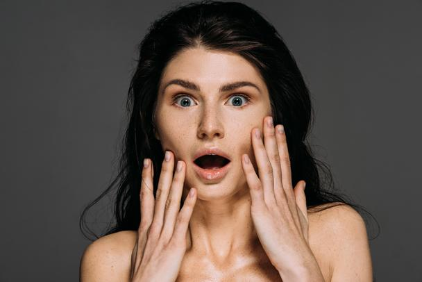 beautiful shocked woman with freckles on face isolated on grey - Photo, Image