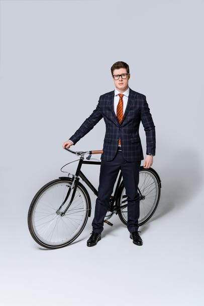 stylish businessman in suit standing with bicycle on grey  - Photo, Image