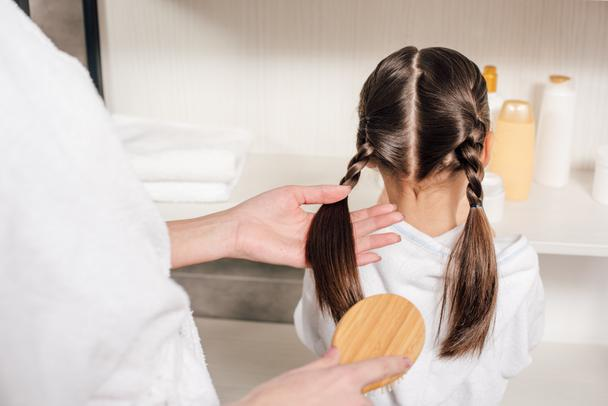 mother in white bathrobe combing daughter hair in bathroom - Photo, Image