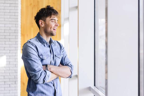 handsome and smiling man with crossed arms looking away at cafe  - Photo, Image