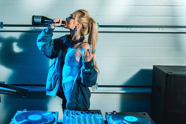 dj woman gesturing near dj mixer while drinking wine from bottle - Photo, Image