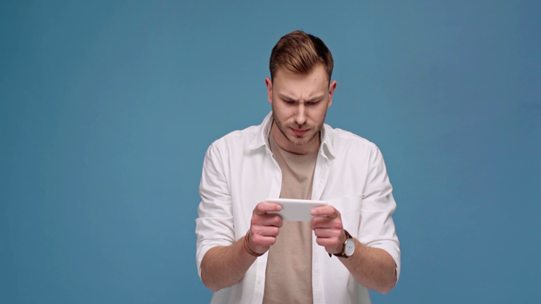 handsome concentrated man palying game on smartphone isolated on blue - Footage, Video