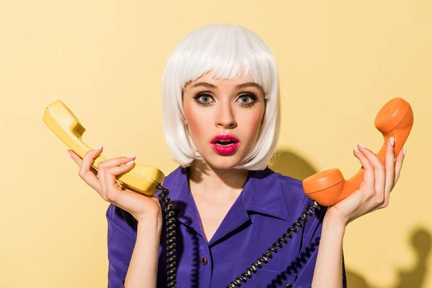 Surprised young woman in wig holding handsets on yellow background - Photo, Image
