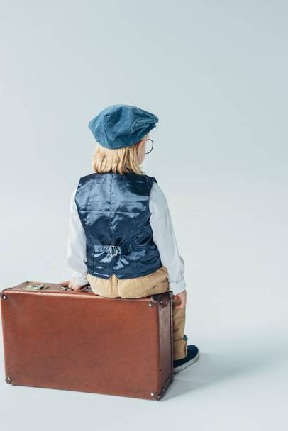 back view of kid in retro vest and cap sitting on suitcase on grey background - Photo, Image