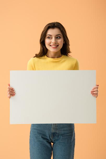 Blissful smiling brunette girl holding blank placard isolated on orange - Photo, Image