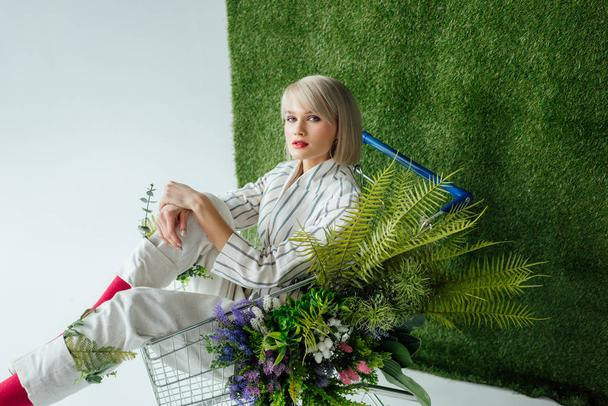 beautiful fashionable girl sitting in shopping cart with fern and flowers on white with green grass - Photo, Image