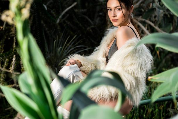 Sexy young woman in white faux fur coat and underwear near plants in botanical garden - Photo, Image