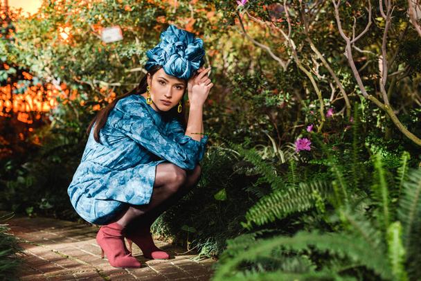 Sad pensive woman in blue dress and turban sitting in botanical garden - Photo, Image