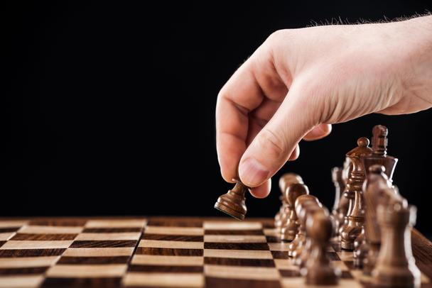 partial view of man doing move on wooden chessboard isolated on black - Photo, Image