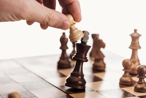 partial view of man holding pawn above wooden chessboard isolated on white - Photo, Image